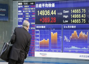 A man looks at an electronic stock board of a securities firm in Tokyo, Thursday, Nov. 14, 2013. (AP Photo/Koji Sasahara)